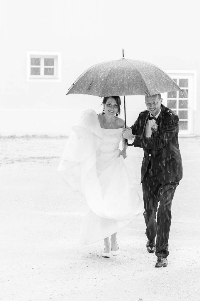 Regenschauer bei Paarshooting in Ulm, Braut und Bräutigam laufen bei Regen unter einem Schirm