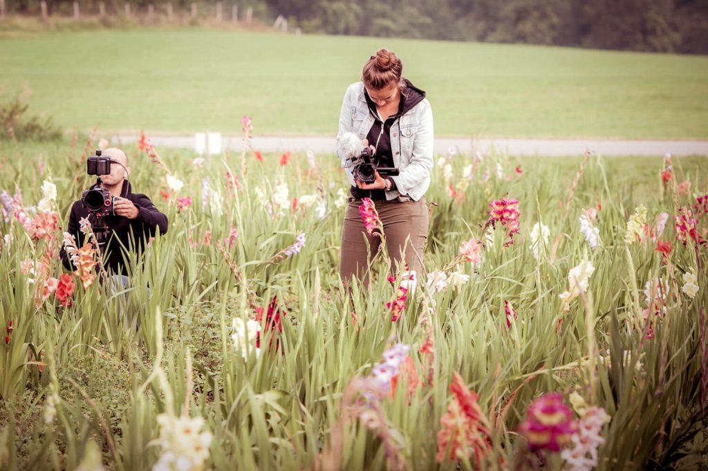 making of Hochzeitsfilm Szene first look, zwei Kameraleute in einer Blumenwiese am Wörthsee